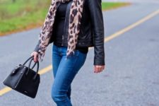 With black shirt, leather jacket, skinny jeans, ankle boots and black bag