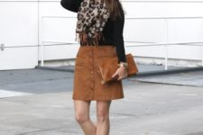 With black shirt, suede skirt, ankle boots and clutch