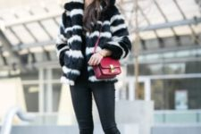 With black skinny pants, mid calf boots and red bag