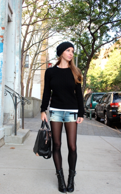 With black sweater, mid calf boots, leather bag and black beanie