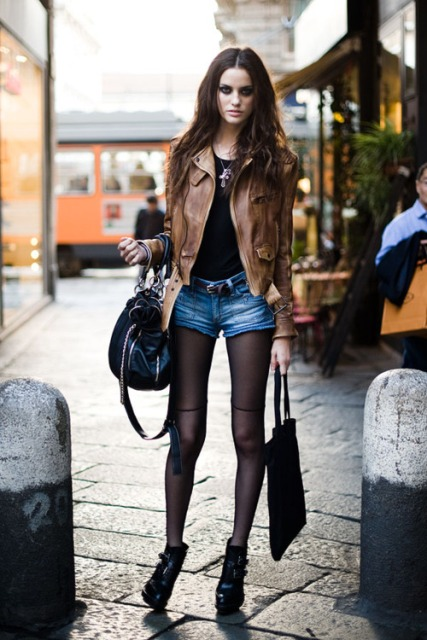 With black t shirt, brown leather jacket, black boots and black bag