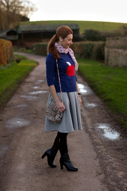 With blue sweater, gray knee length skirt, high boots and gray bag