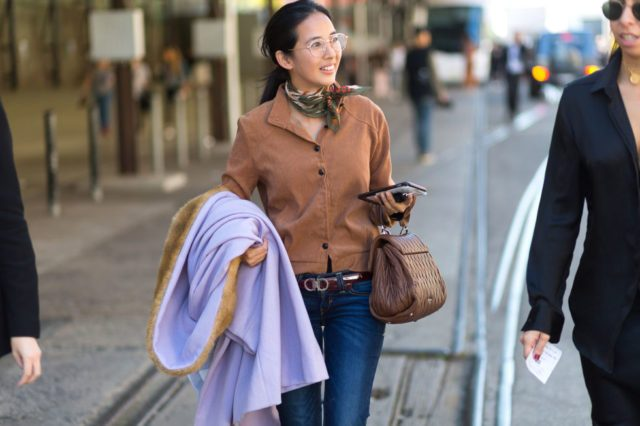 With brown shirt, jeans, lilac coat and brown bag