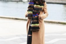 With camel coat, distressed pants and ankle boots