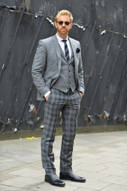 With gray blazer, gray vest, white shirt, printed tie and black shoes