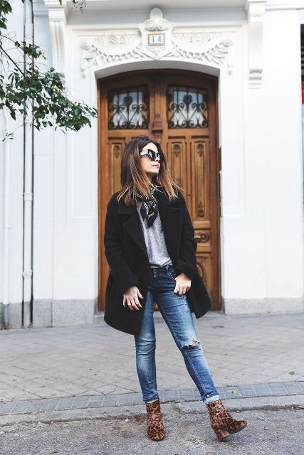 With gray shirt, black coat, distressed jeansa and leopard boots