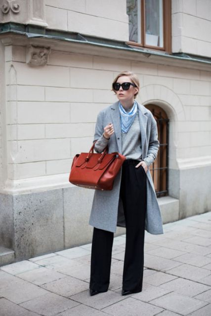 With gray shirt, gray knee length coat, wide leg pants and red bag