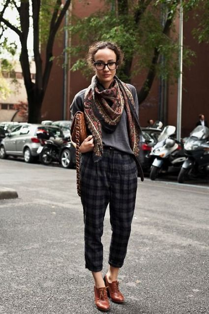 With gray shirt, printed scarf, brown ankle boots and clutch