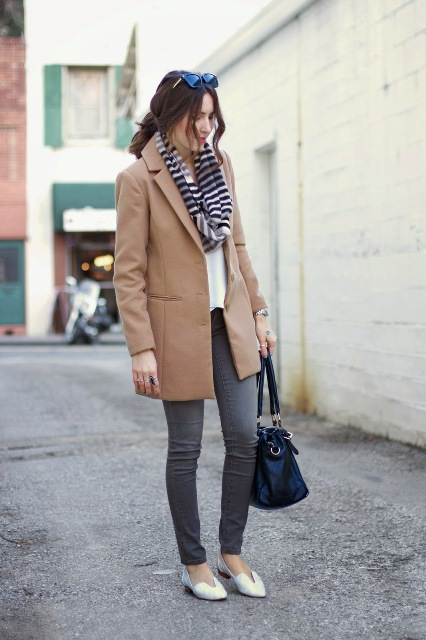 With gray skinny pants, white shoes, white blouse, camel coat and black bag