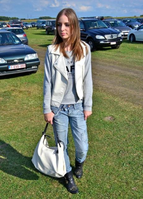 With gray sweatshirt, jeans, black boots and white bag