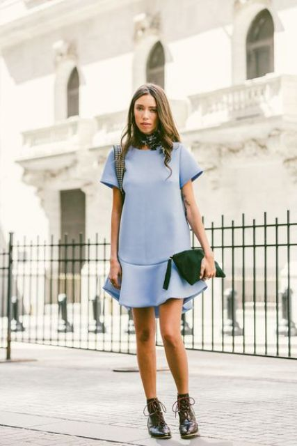 With pastel colored dress, green clutch and lace up boots