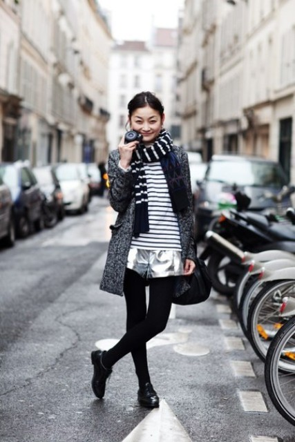 With striped shirt, silver shorts, black tights, black flat boots, tweed coat and black bag