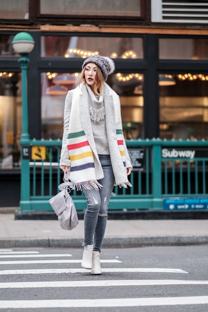With turtleneck sweater, distressed jeans, white boots, beanie and backpack