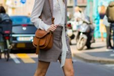 With white blouse, printed vest, printed shorts, lace up boots and brown bag