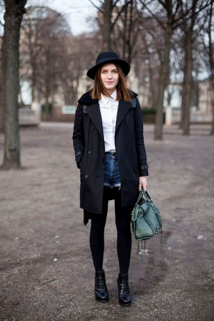 With white button down shirt, black wide brim hat, black tights, ankle boots, black coat and green bag