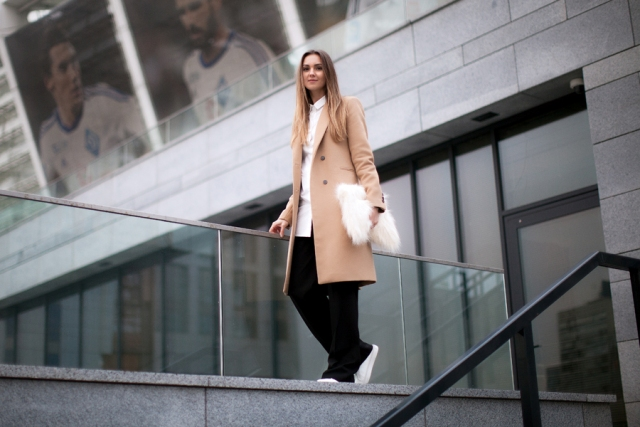 With white button down shirt, camel coat, wide-leg pants and white sneakers