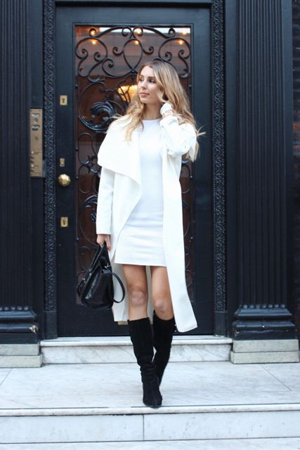 With white dress, black high boots and black bag