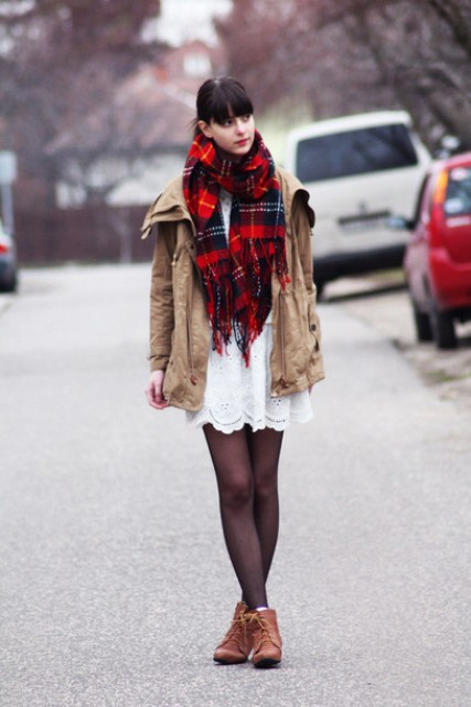 With white dress, brown boots and beige parka coat