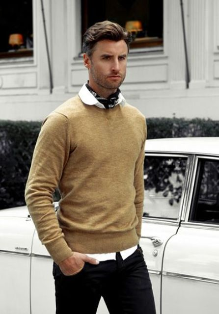 With white shirt, black pants and camel sweater
