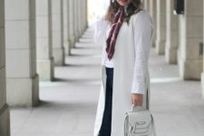 With white shirt, white long vest, flare jeans, heels and white bag