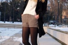 With white sweater, black coat, flat ankle boots and beanie