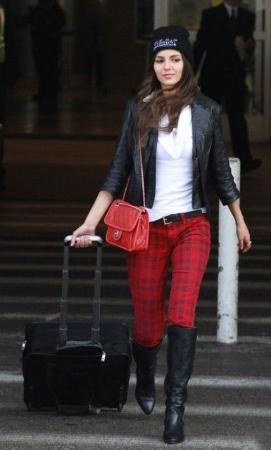 With white sweater, black leather jacket, beanie, high boots and red bag