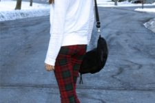 With white sweatshirt, black ankle boots and black bag