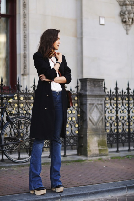 With white t shirt, black coat, flare jeans and platform shoes