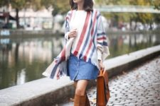 With white t-shirt, denim skirt, high boots and brown leather bag