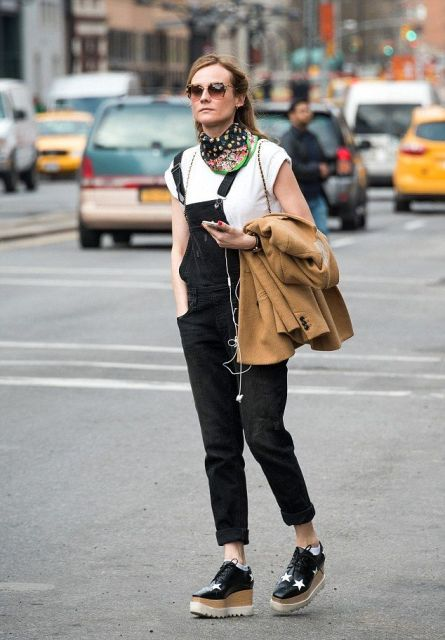 With white t-shirt, jumpsuit, platform shoes and brown blazer