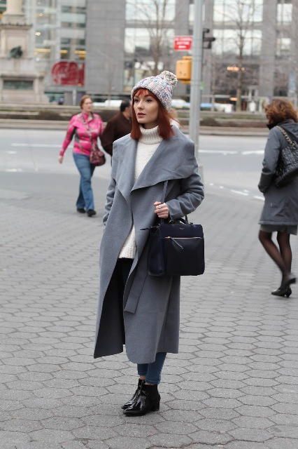 With white turtleneck sweater, jeans, ankle boots, beanie and black leather bag