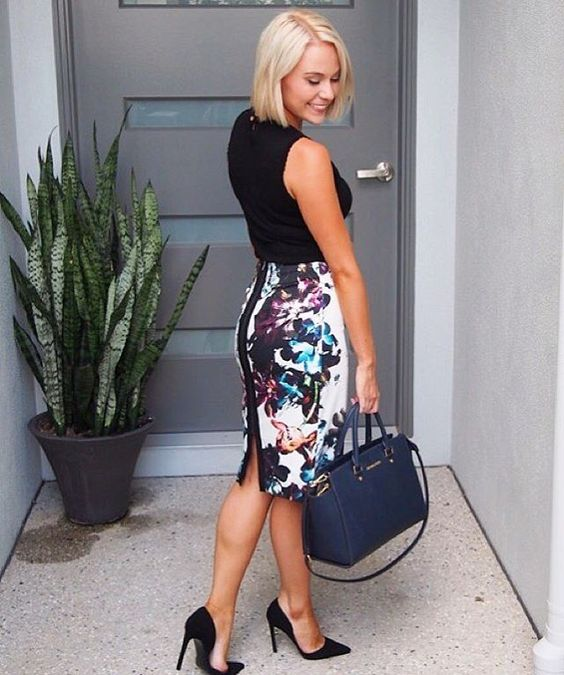 a black sleeveless top, a floral pencil skirt with a slit, black heels and a navy bag