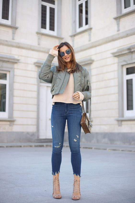 ripped cropped jeans, metallic strappy shoes, a neutral sweater and an olive grene cropped bomber