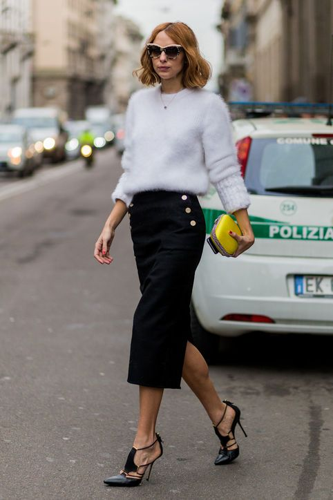 a black midi skirt with a slit and buttons, a white angora sweater, black heels and small yellow clutch