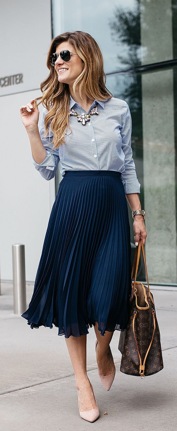 a navy pleated midi skirt, a striped blue shirt, a statement necklace and nude heels