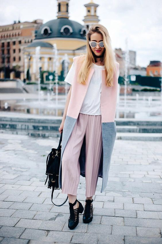 a white tee, pink pleated cropped pants, a color block grey and pink sleeveless coat and black shoes