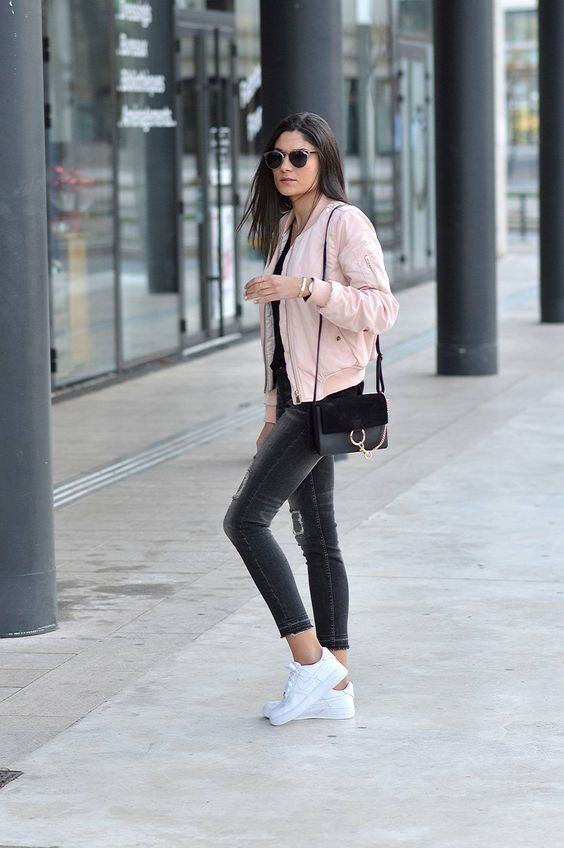 black cropped jeans, a black top, a light pink bomber jacket, white sneakers and a black bag