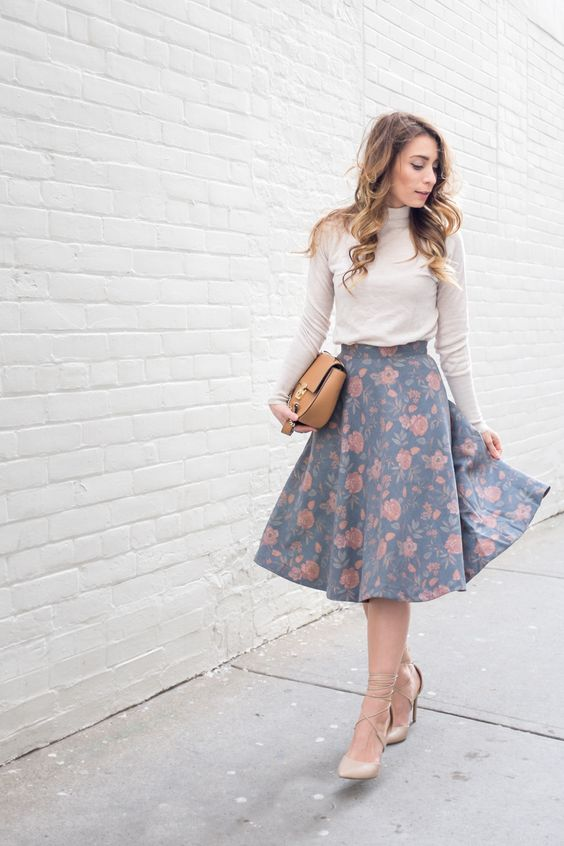 a floral muted-color A-line midi skirt, strappy heels, a neutral turtleneck and a tan bag