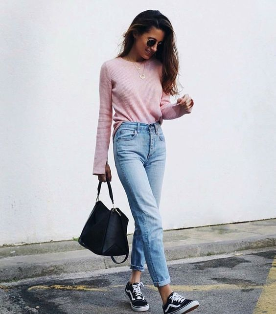 a pink sweater, blue high waisted cuffed jeans and black Vans