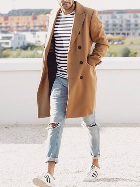 distressed jeans, white trainers, a striped t-shirt and a camel coat