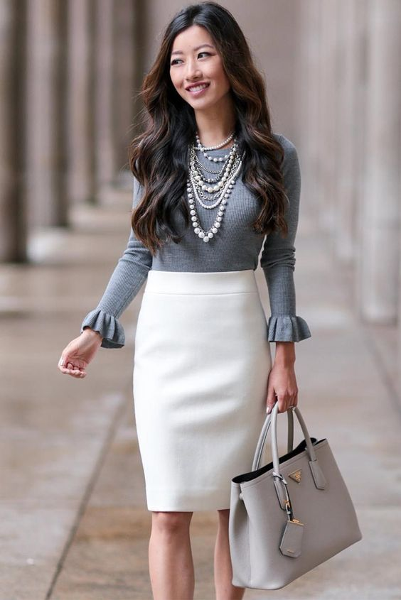 a creamy pencil knee skirt, a grey top with ruffled sleeves, layered necklaces
