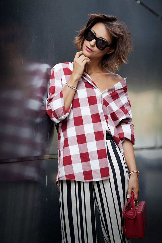black and white striped pants, a red gingham shirt and a red bag