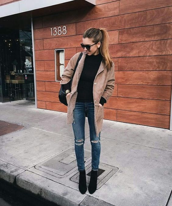 blue ripped skinnies, a black turtleneck, black suede boots and a camel short coat