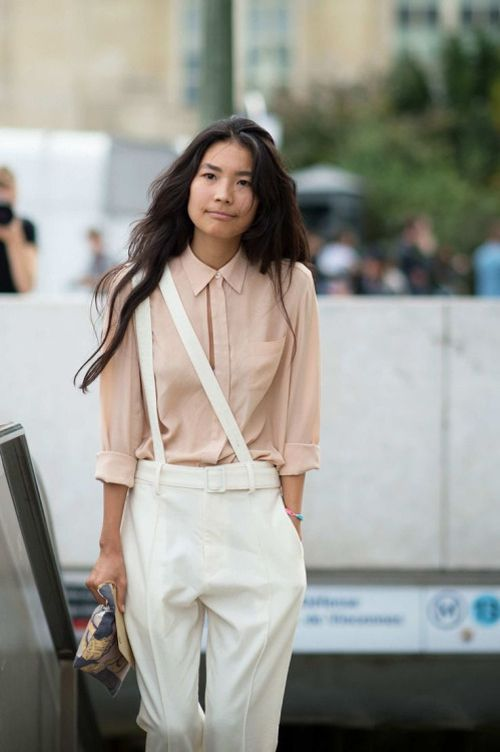 a blush shirt and creamy trousers with suspenders worn on one shoulder