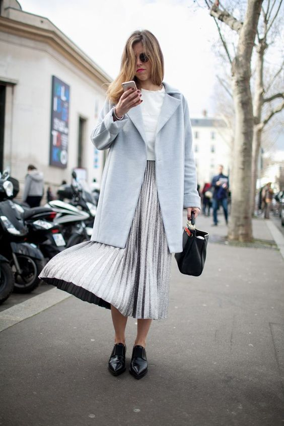 a white tee, a metallic pleated midi, black flat shoes and a powder blue coat for an elegant casual look