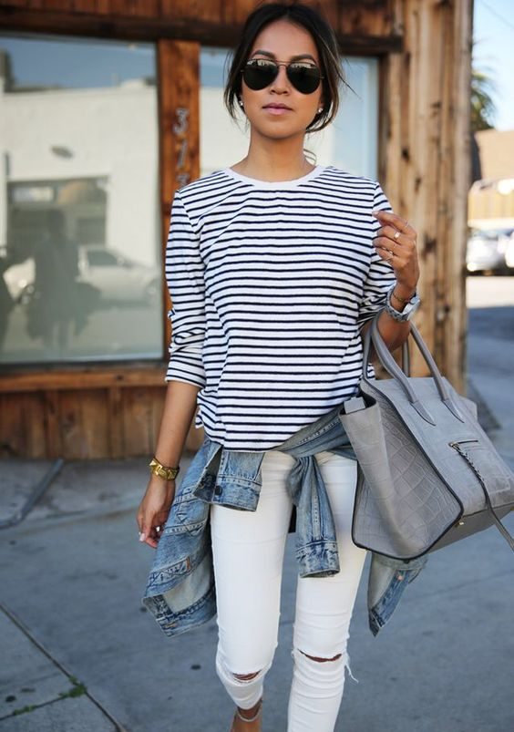 white ripped jeans, a striped long sleeve, a denim jacket and a grey bag