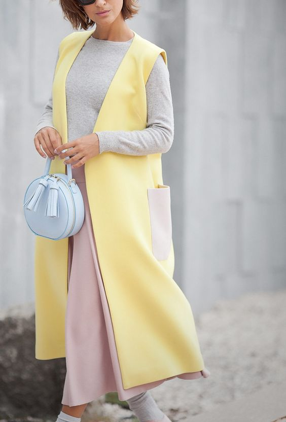 a grey long sleeve, a pink midi skirt, a yellow sleeveless coat and a powder blue bag
