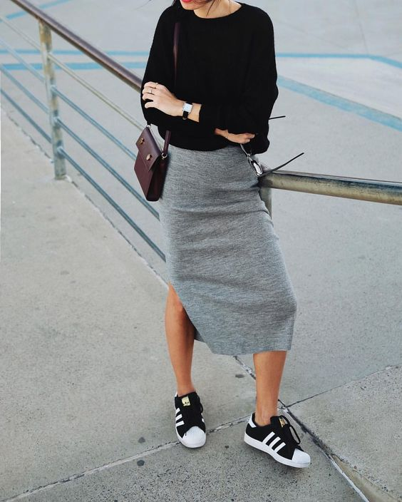 a grey pincil midi skirt with a slit, black and white trainers, a black top and a burgundy bag