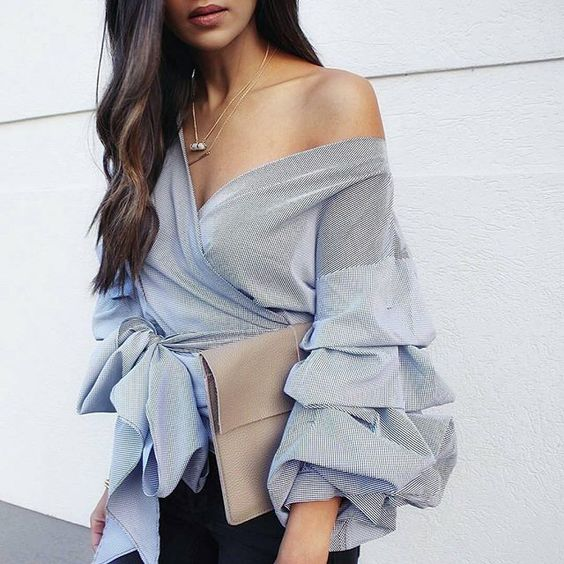 black skinnies, a wrap one shoulder blouse with ruffled sleeves and a neutral clutch