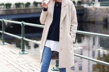 08 blue jeans, a white tee, a black pullover, white sneakers and a tan trench